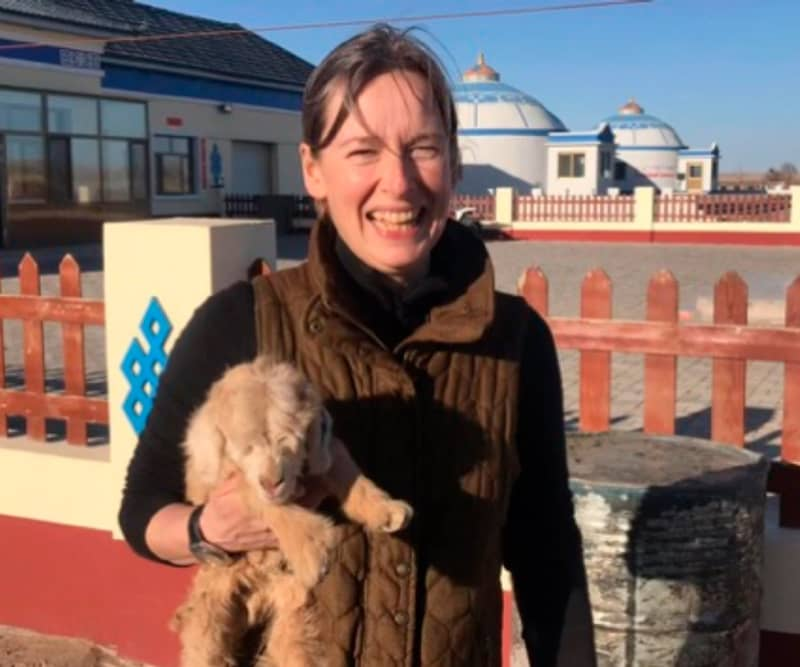Anna Heaton with a cashmere goat kid in Inner Mongolia