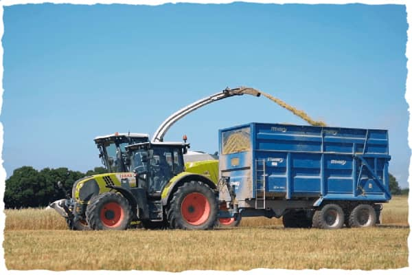 Combine and tractor cropping in a field